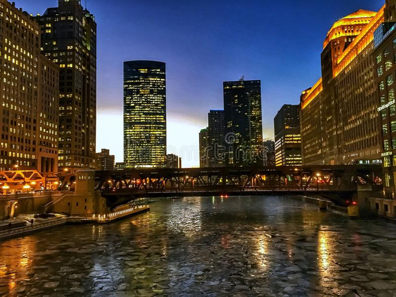 View of frozen Chicago River and elevated track during evening sunset at rush hour. View of frozen Chicago River and elevated track during evening sunset at stock image