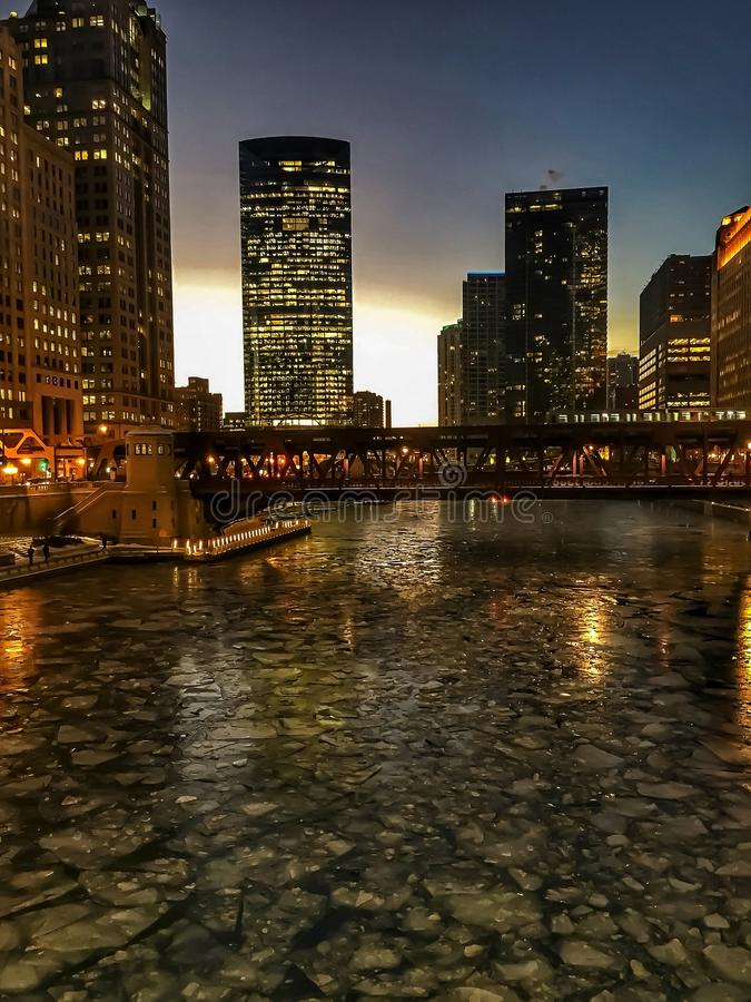 View of frozen Chicago River and elevated track during evening sunset at rush hour with ice chunks on river. View of frozen Chicago River and elevated track royalty free stock photography