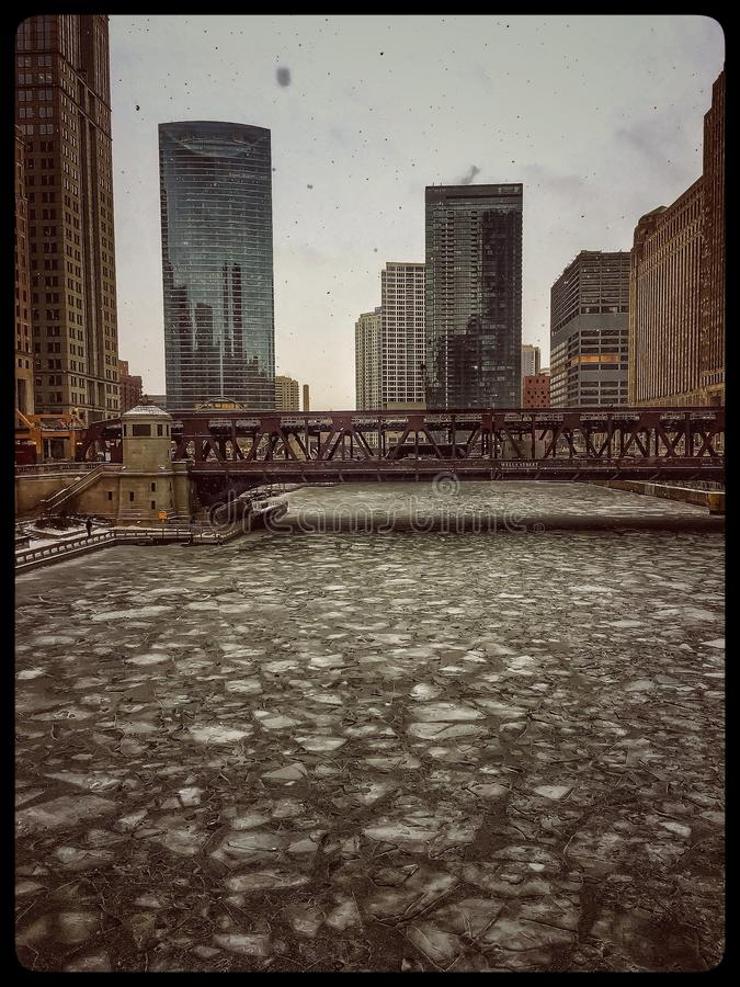View of frozen Chicago River and elevated track during heavy snowfall. View of frozen Chicago River and elevated track during heavy snowfall on frigid January royalty free stock image