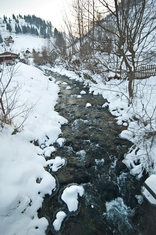 View of frozen river countryside. Brook in snowy landscape. Romanian small river in winter scenery, Romania, Moeciu. Wild brook royalty free stock photo