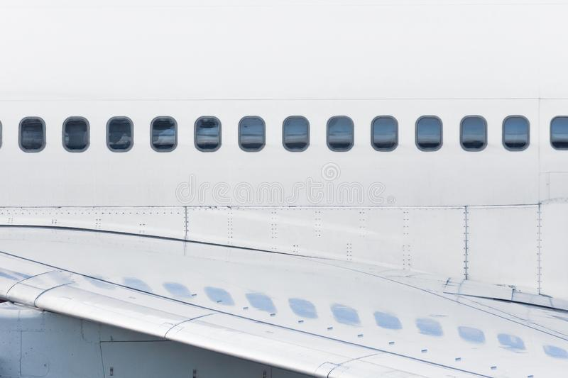 View of the fuselage of the aircraft and many windows, with reflection on the wing.  stock photos