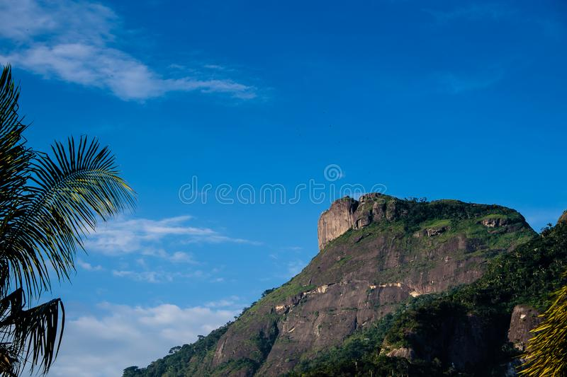 View of the Gavea Stone, seen from the street with houses on the hill during late afternoon. Barra da Tijuca, Rio de Janeiro.  royalty free stock photo