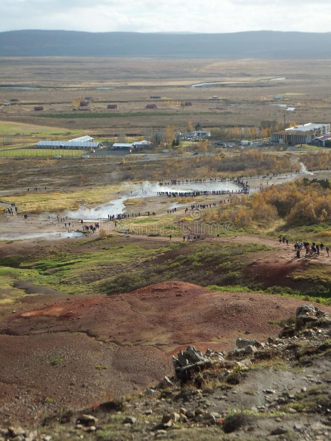 View of the geyser geothermal area in Haukadalur Valley, Iceland, with small figures of people flocking to see the eruption. View of the geyser geothermal area stock photos