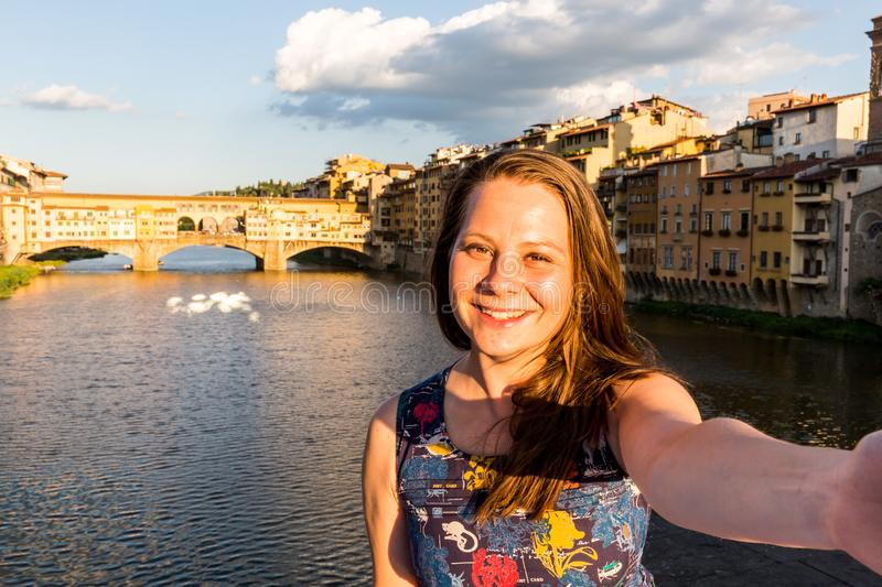 Girl in front of the Ponte Vecchio in Florence, Italy in summer stock image