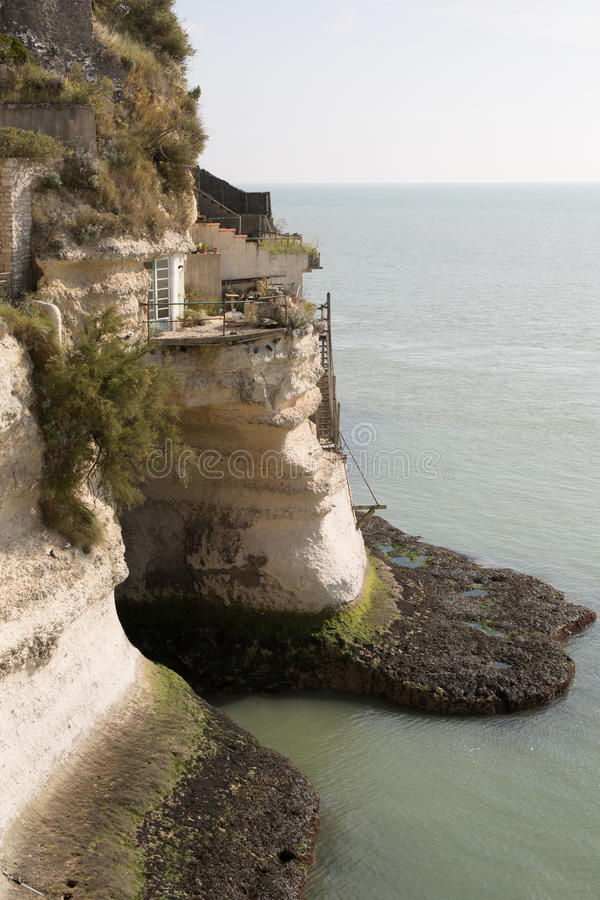 View from the Gironde estuary with the limestone cliff. Of the village of Meschers sur Gironde and its troglodytic houses and traditionnal typical wooden stock photo