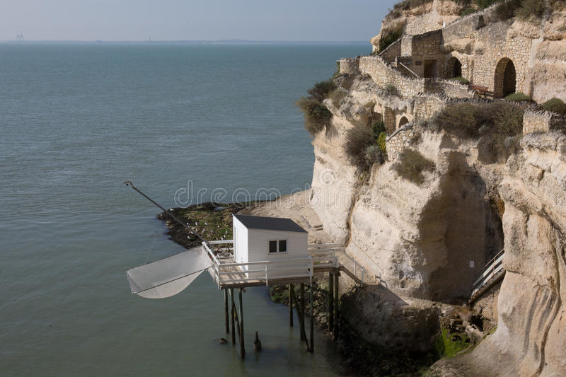 View from the Gironde estuary with the limestone cliff. Of the village of Meschers sur Gironde and its troglodytic houses and traditionnal typical wooden royalty free stock photography