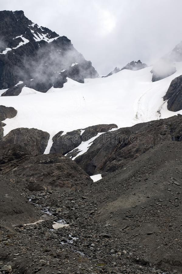 View of glacier with 2 climbers traversing stock photo