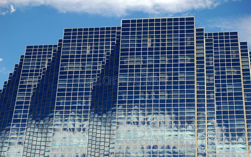Glass Skyline Reflection, Modern Buildings. View of glass building with mirrored windows refection the sky and clouds creating an abstract mosaic pattern stock image