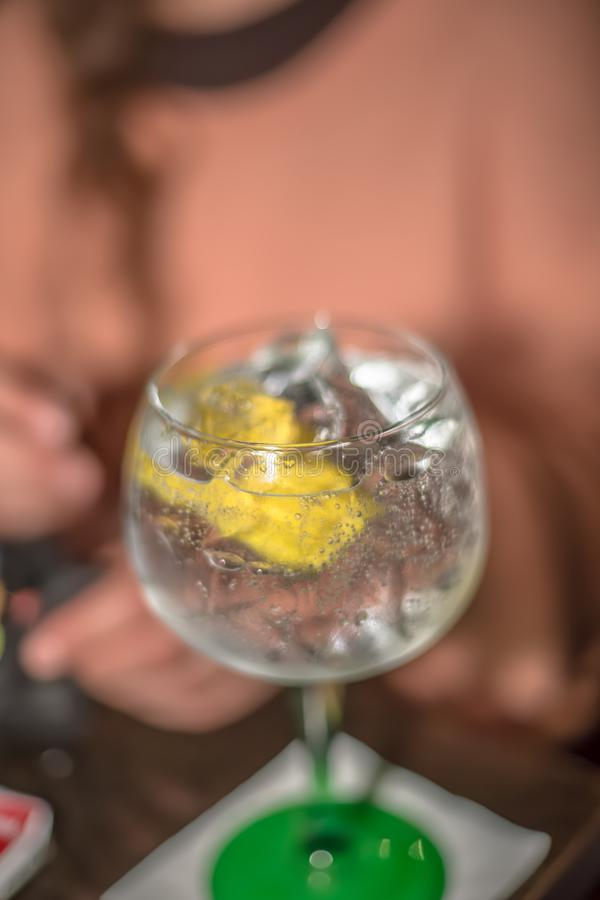 View of glass of refreshing gin, with lemon and ice, classic cup, with green foot stock image
