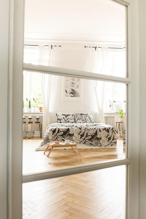View through a glass and wood door to a spacious white bedroom interior with a bed with linen standing on a herringbone parquet fl. Oor. Real photo royalty free stock image