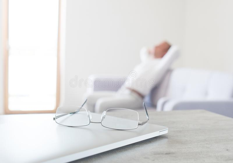 View of glasses lying on the modern laptop with hard thinking man sitting on sofa on the background stock image