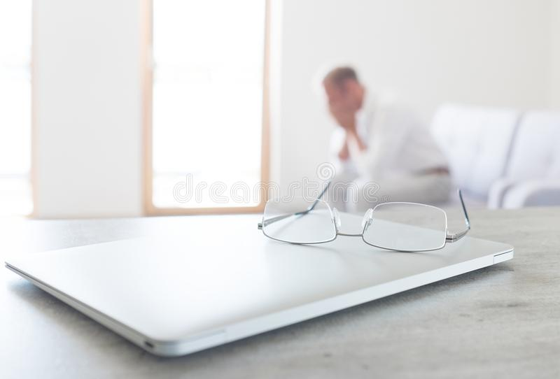View of glasses lying on the modern laptop with hard thinking man sitting on sofa on the background royalty free stock photos
