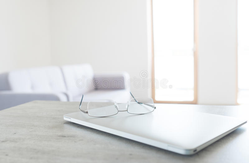 View of glasses lying on the modern laptop with scandinavian design interior stock images