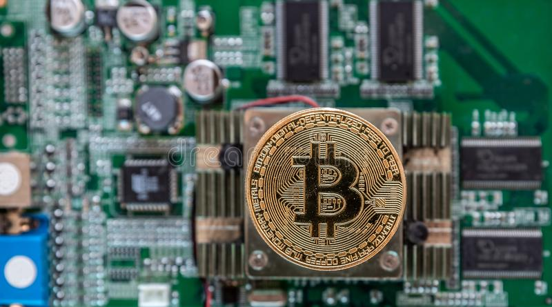 View of a golden bitcoin placed on a chipset of a graphics card with lots of circuitry and processors. View of a large golden bitcoin placed on a chipset of a royalty free stock photo