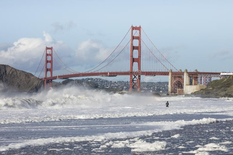View of the Golden Gate Bridge with man fishing in huge waves. View of the Golden Gate Bridge from Baker beach with man fishing in huge waves royalty free stock images