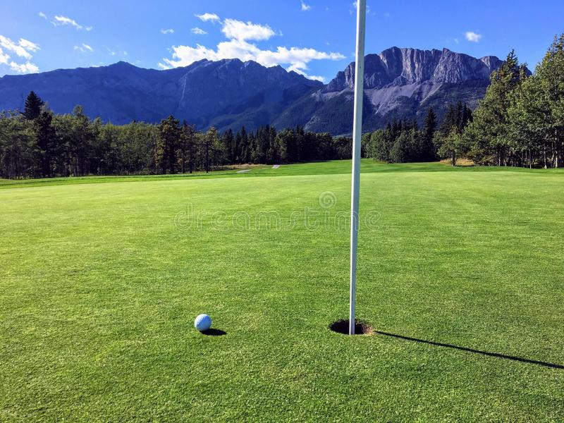 A view of a golf ball on a green close to the hole with the mountains and forest in the background on a beautiful summer day. royalty free stock image