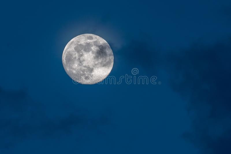 Gorgeous full moon in a dark blue night sky gets covered by soft wispy dark clouds stock photography