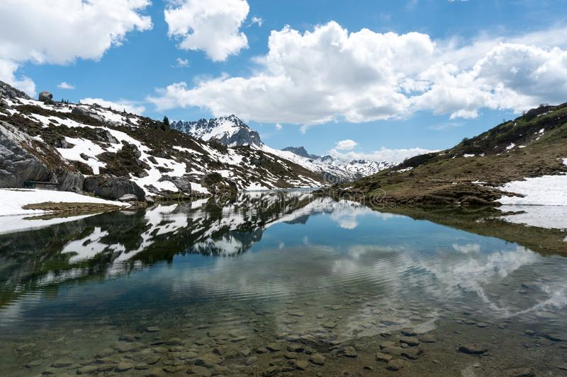 Gorgeous mountain lake in the Alps with reflections and snow remnants royalty free stock image