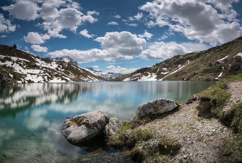 Gorgeous mountain lake in the Alps with reflections and snow remnants stock photography