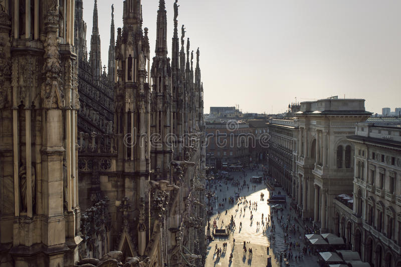 View from the gothic cathedral Duomo di Milano, Italy. Silhouettes of tiny people far below royalty free stock photography