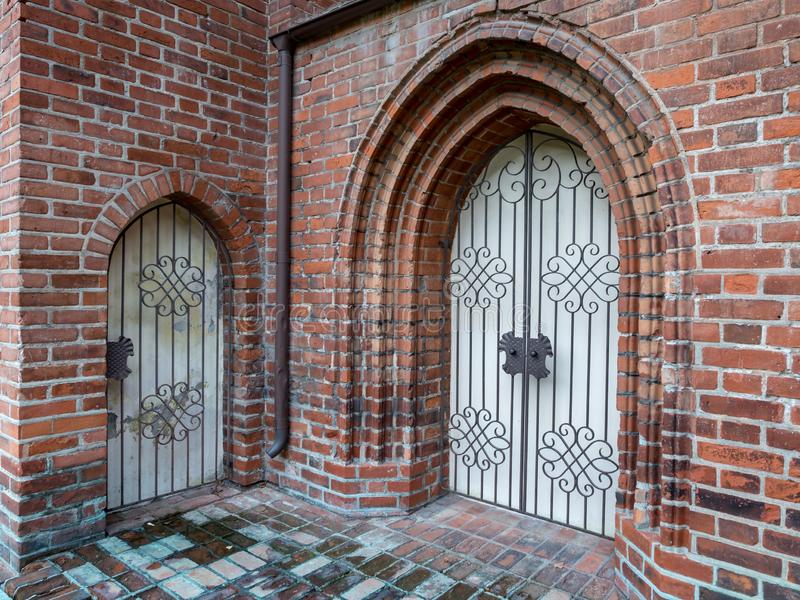 Gothic doors in the brick wall with metal cells. View of the gothic doors in the brick wall stock photography