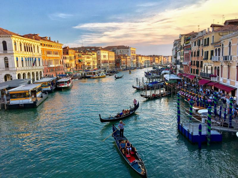 A view of the Grand Canal from the Rialto Bridge in Venice, Italy.  It is a busy summer evening with the canal full of water taxis stock images