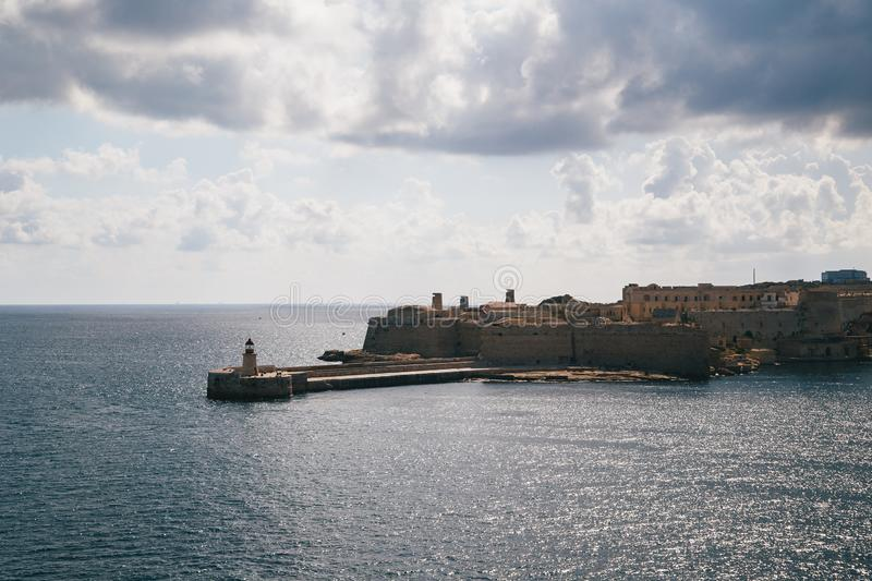 View of the Grand Harbour entrance and old medieval Ricasoli East Breakwater with red lighthouse and Fort Ricasoli seen from stock photos