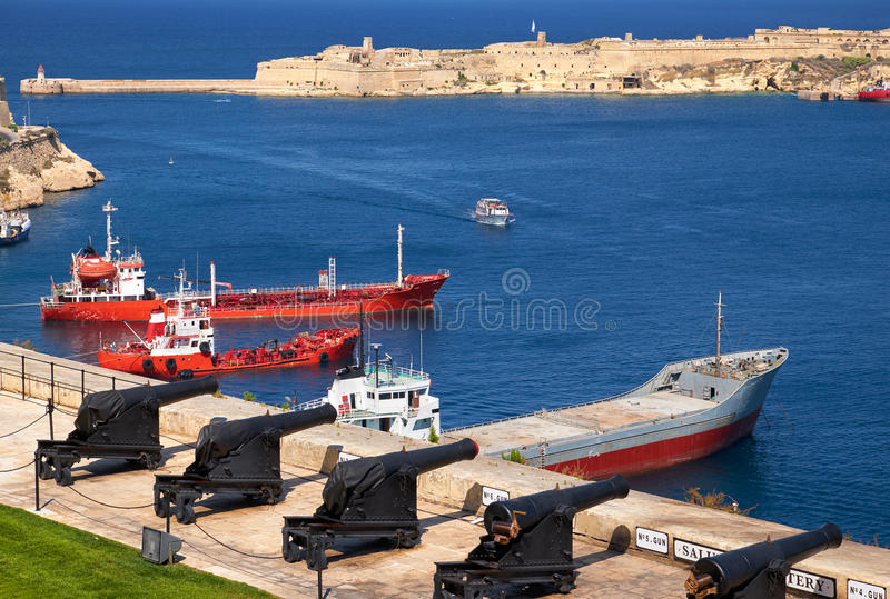 The view of Grand Harbour and the Saluting Battery from the Upper Barrakka Gardens, Valletta, Malta. The view of Grand Harbour with moored cargo ships and the stock photography