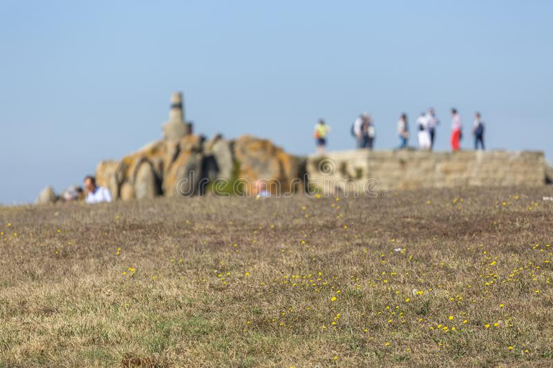 View of grass texture in perspective, background blur with rock and people, near the sea royalty free stock photos