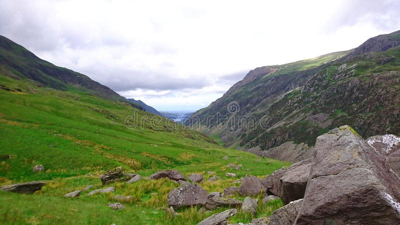 View across fields and valley towards base of mountain on PYG trail on Mount Snowdon in Snowdonia National Park, Wales, UK royalty free stock images