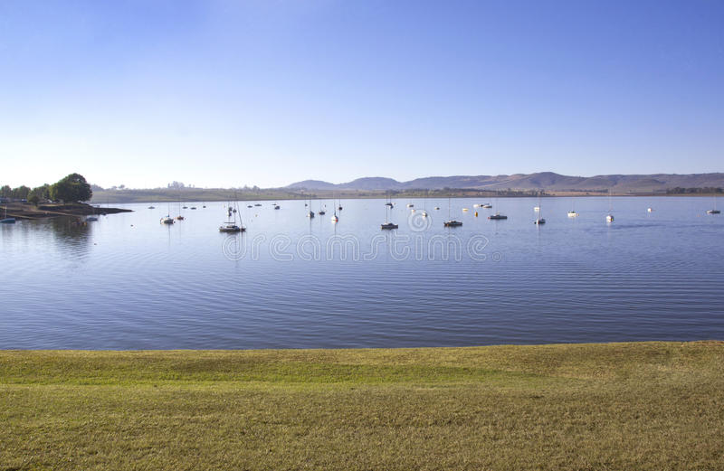 View from Grass Verge of Yachts Moored on Dam. View from grass verge of yachts moored on the midmar dam in the natal midlands, Howick, KwaZulu-Natal South Africa stock images