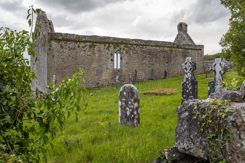 A view through grave stone and foliage of the abanoned ruins of Killone Abbey that was built in 1190 and sits on the banks of the. Killone Lake, just outside royalty free stock images