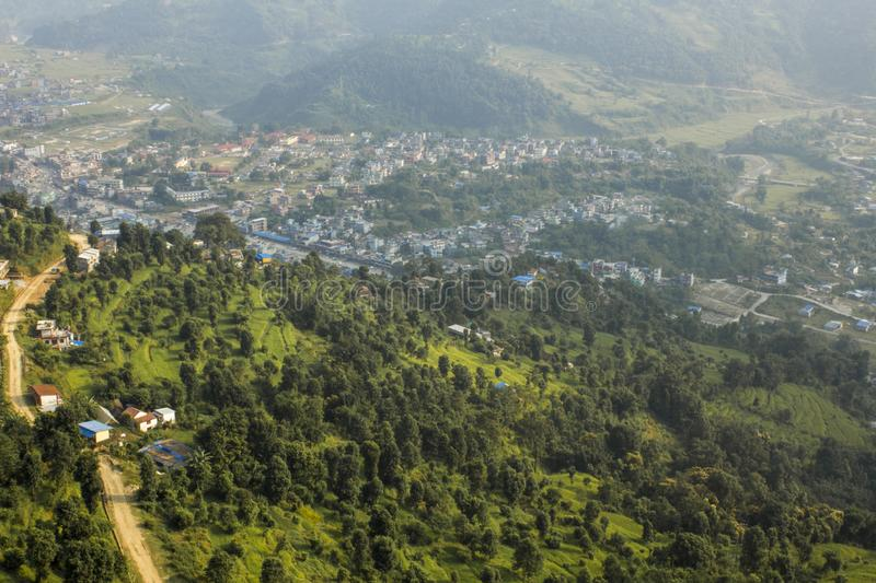 A view from a great height to the green slope of the mountain and the city in the mountain valley against the background of the. View from a great height to the stock photos