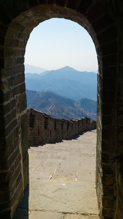 View of Great Wall of China through the brick rounded door leading from watchtower, China. stock photo
