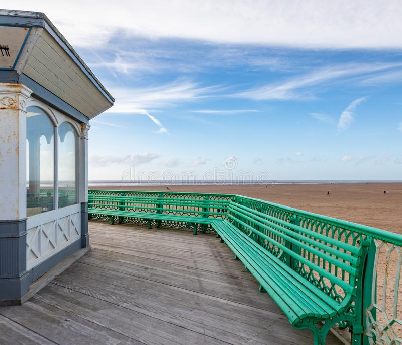 A view of a green bench on St Annes on Sea Pier North West England February 2019. A bench, footpath and building on St Annes on Sea Pier royalty free stock images