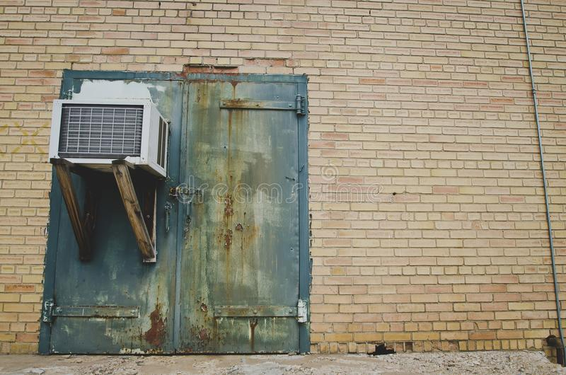 A old rusty green door with a ac unit at the old factory royalty free stock photography
