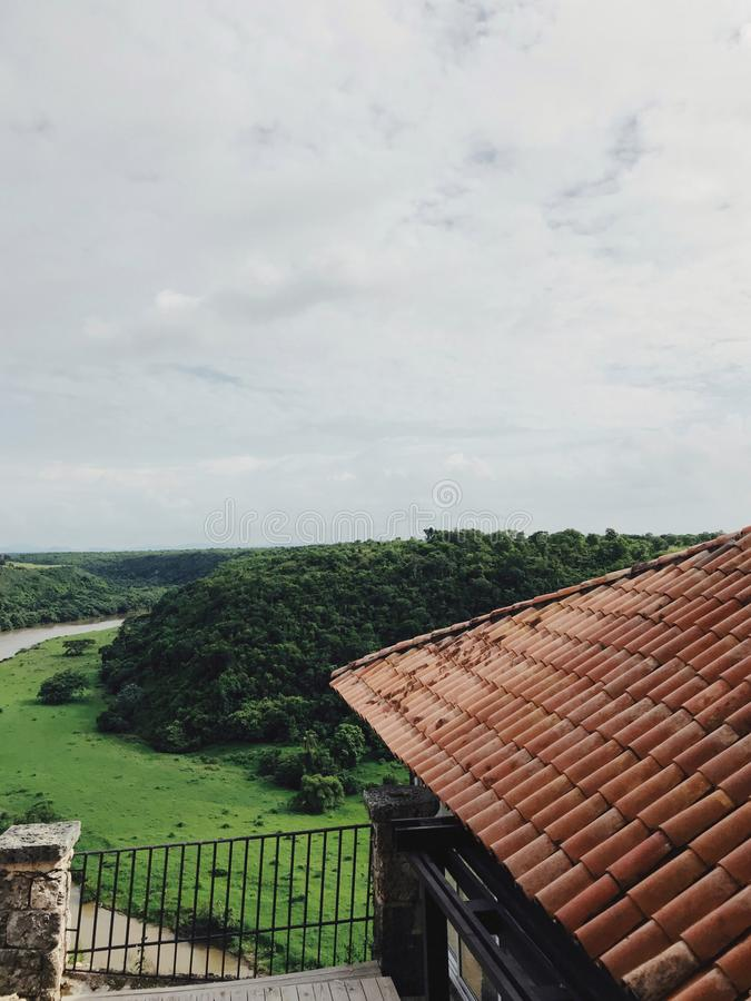 View at green fields of altos de chavon from the red roof of antique-like building. Tile roof top of antique-like building of Altos de Chavon in dominican stock photos