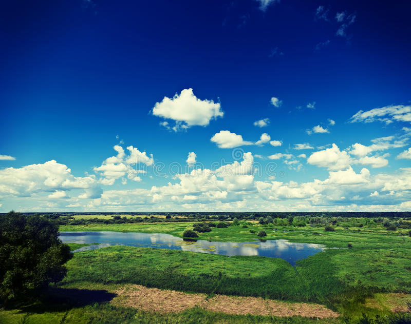 view on green spring flood field with beautiful cloudy sky instagram stile stock photography