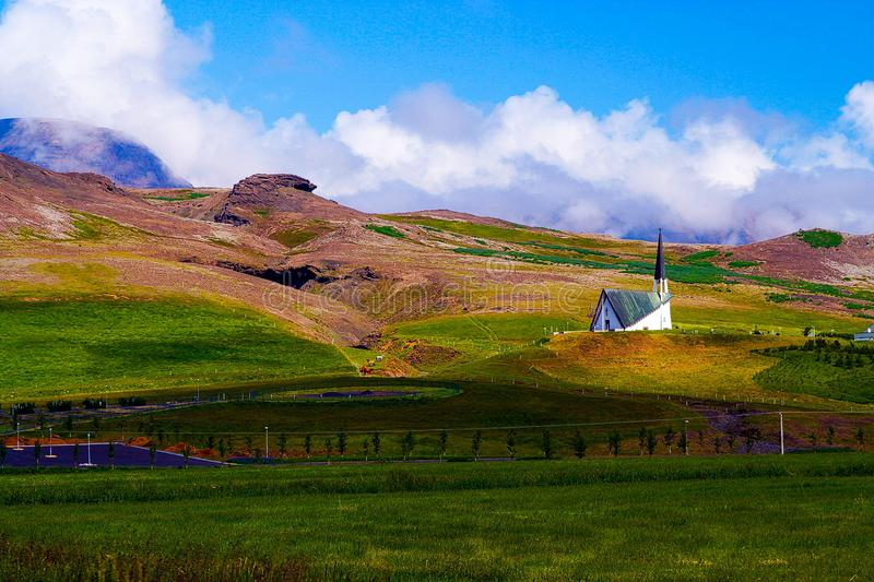 View into green valley with  church on hill in rural landscape. Iceland stock photos