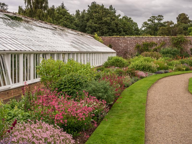 Greenhouse in a garden. A view of a greenhouse and the surrounding gardens royalty free stock photo
