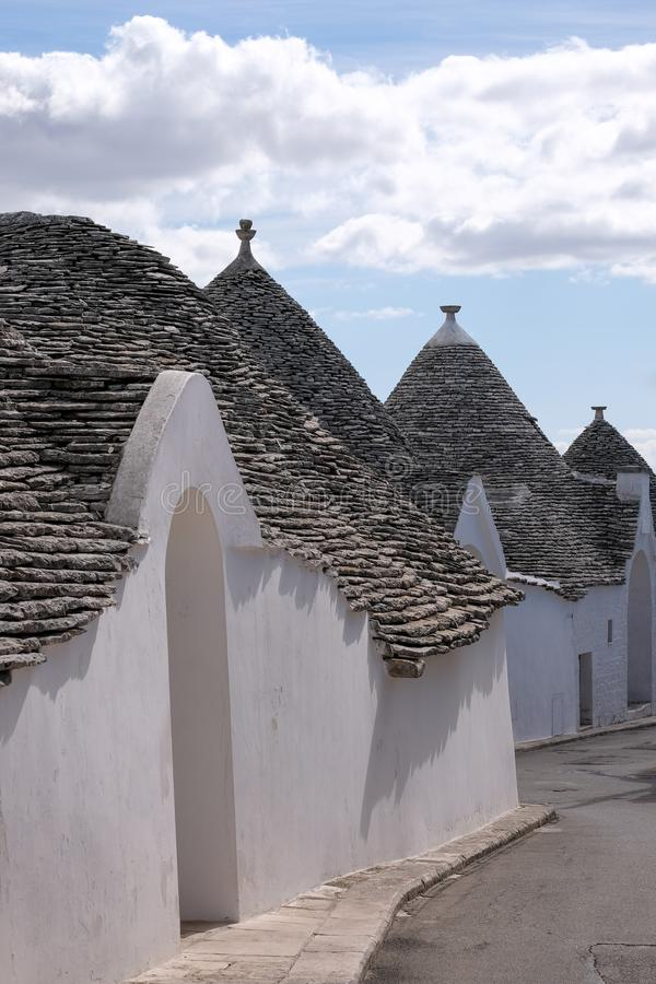 View of group of traditional trullo houses in the Aia Piccola residential area of Alberobello in the Itria Valley, Puglia Italy. View of group of traditional royalty free stock image