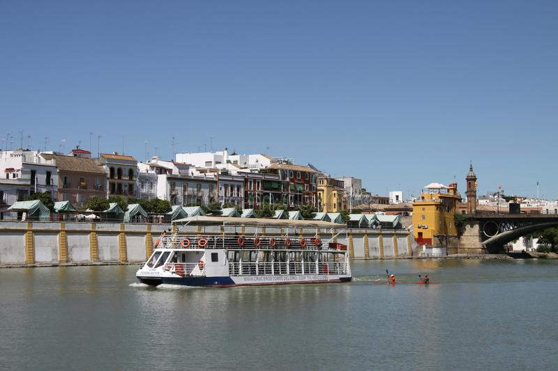 View of the Guadalquivir River and the Isabella II Bridge in Seville. SEVILLE, SPAIN - JULY 17, 2011: View of the Guadalquivir River and the Isabella II Bridge royalty free stock photography