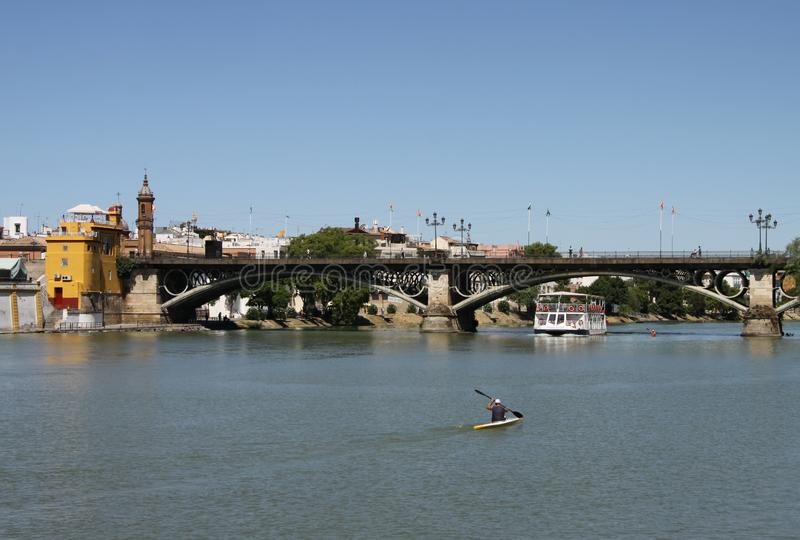 View of the Guadalquivir River and the Isabella II Bridge in Seville. SEVILLE, SPAIN - JULY 17, 2011: View of the Guadalquivir River and the Isabella II Bridge stock photography