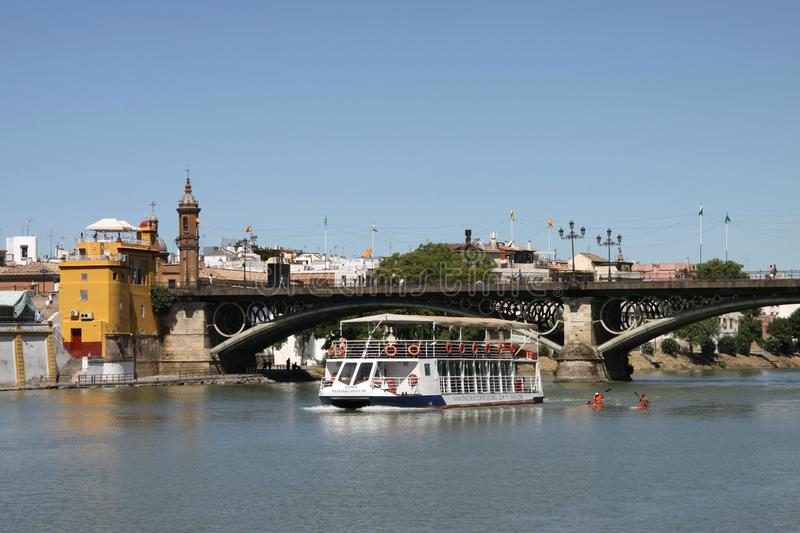 View of the Guadalquivir River and the Isabella II Bridge in Seville. SEVILLE, SPAIN - JULY 17, 2011: View of the Guadalquivir River and the Isabella II Bridge stock image