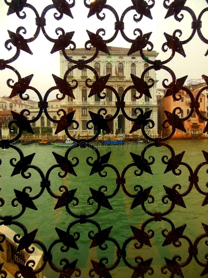 View from the Guggenheim Palazzo Venice on a Rainy Day. An unusual and provocative view through the elaborate ironwork that frames a window at the Guggenheim stock photo
