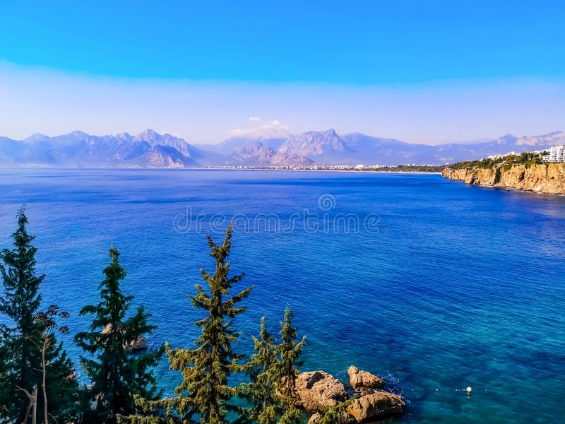 View of the Gulf of Antalya in the Mediterranean Sea and the Taurus Mountains on the horizon. Amazing landscape of the Turkish. Riviera with a city on a cliff royalty free stock photos