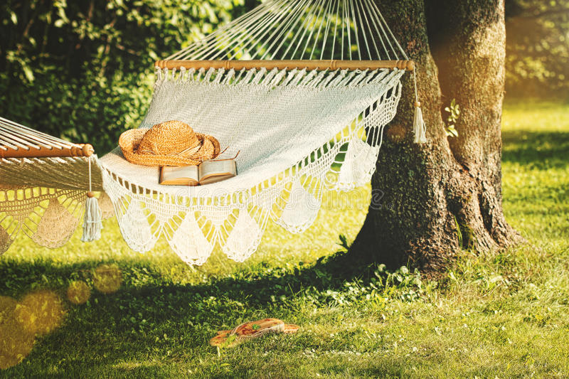 View of hammock and book on a summer day. View of hammock and book on a sunny summer day stock photo