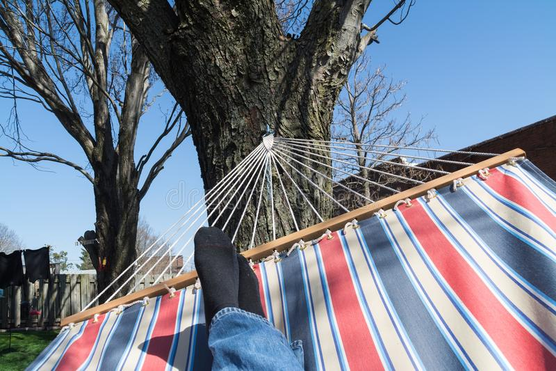 View from hammock. Man`s feet on hammock with backyard in background on a beautiful Spring afternoon stock images