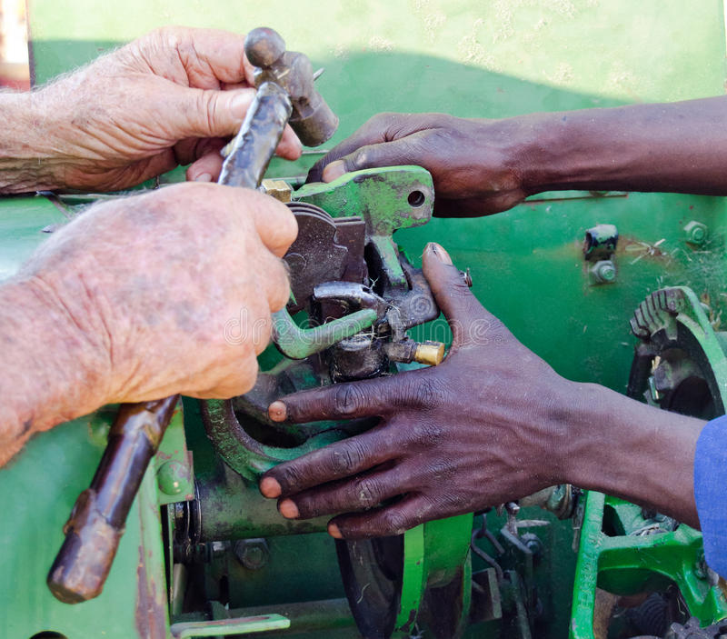 View of hands repairing old bailer. Two pairs of hands repairing an old bailer royalty free stock images
