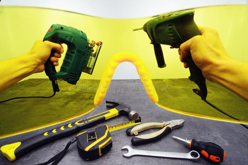 Hands with a drill and electric jig saw in the background of tools through yellow protective glasses. First person view. royalty free stock photos